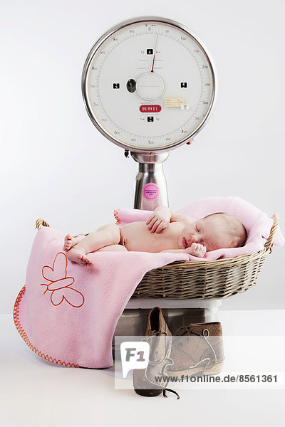 Baby liegt in einem Korb auf einer Waage