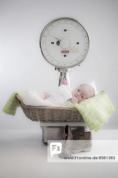 Baby liegt in einem Korb auf einer Waage Baby liegt in einem Korb auf einer Waage