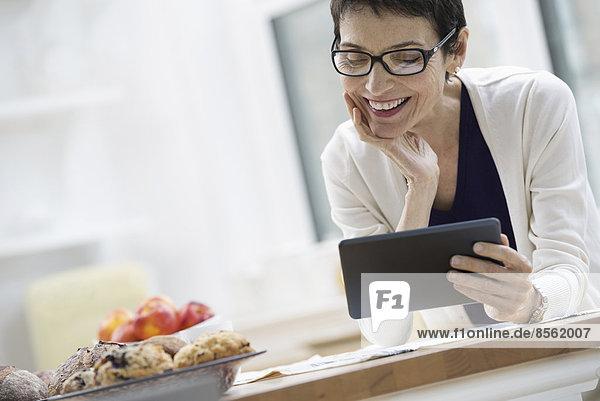 Eine Büro- oder Wohnungseinrichtung in New York City. Eine für die Arbeit gekleidete Frau in cremefarbener Jacke  die eine Tasse Kaffee hält. Sie prüft ihr digitales Tablett.