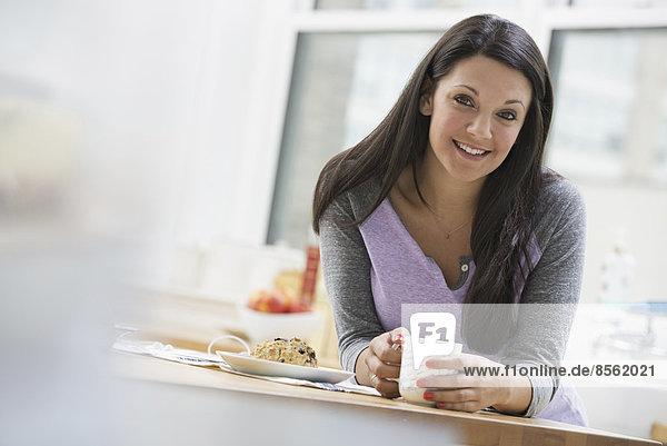 Eine Büro- oder Wohnungseinrichtung in New York City. Eine junge Frau mit langen schwarzen Haaren  die eine Tasse Kaffee trinkt.