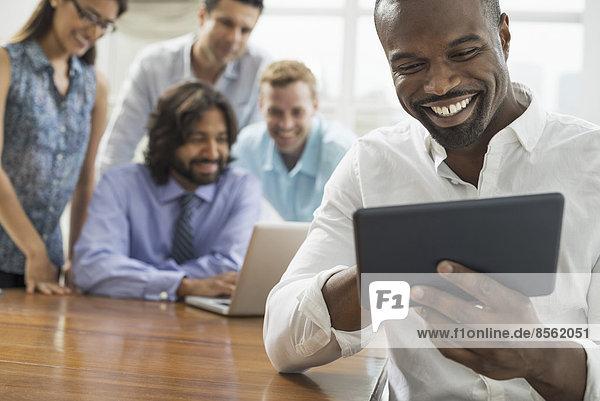 Geschäftsleute versammelten sich in einem Büro in der Stadt. Ein Team von fünf Personen  Männer und Frauen  versammelte sich um einen Laptop.