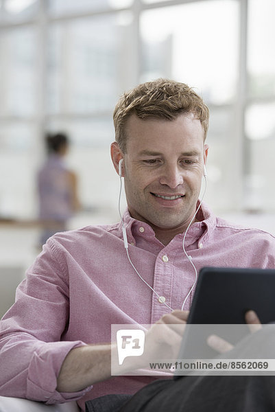 Ein Großraumbüro in New York City. Ein Mann in einem rosa Hemd sitzt lächelnd und benutzt ein digitales Tablet.