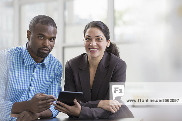 Fachleute im Büro. Ein heller und luftiger Arbeitsplatz. Zwei Personen sitzen an einem Schreibtisch und benutzen ein digitales Tablett. Arbeitskollegen.