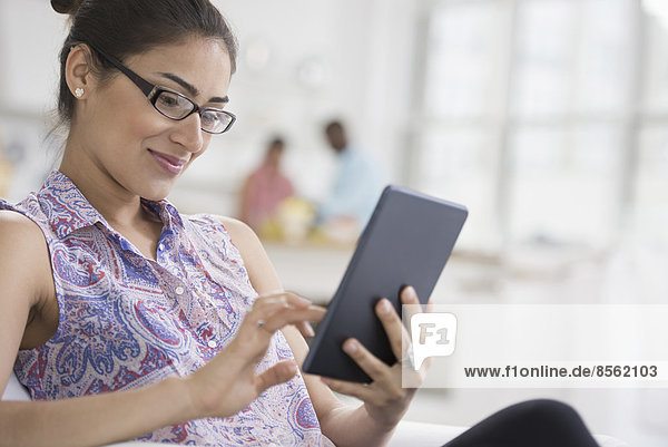 Professionals in the office. A light and airy place of work. A young woman seated using a digital tablet.