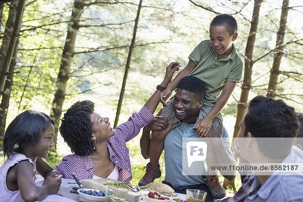Ein Familienpicknick im Schatten hoher Bäume. Ein kleiner Junge sitzt auf den Schultern seines Vaters.