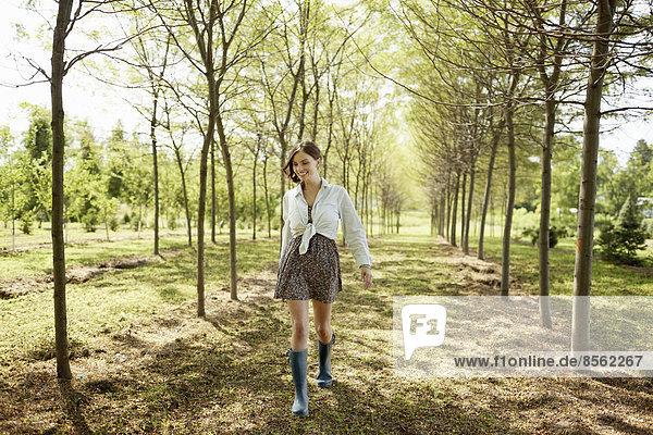 Eine junge Frau geht eine Baumallee im Wald entlang.