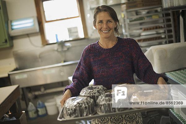 Eine Frau in einer Küche  die ein Tablett mit eisgekühlten  frisch gebackenen Kuchen trägt.