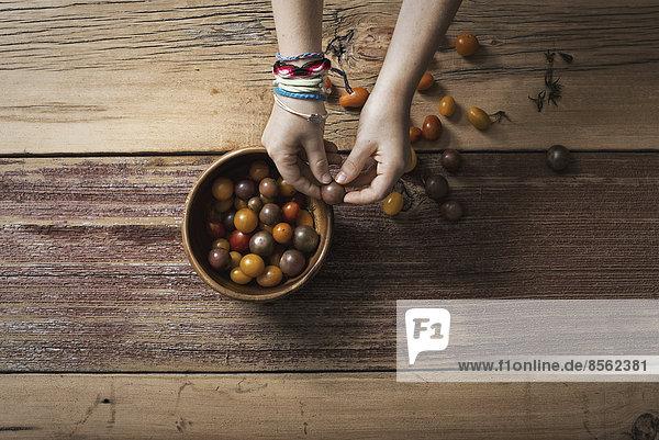 Eine runde Schüssel mit kleinen Tomaten in verschiedenen Farben  die von einer Person sortiert und gepflückt werden. Eine Tischplatte aus Holz.