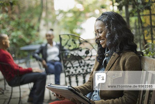 Szenen aus dem städtischen Leben in New York City. Eine Gruppe von Menschen sitzt auf einer Terrasse im Freien. Eine Frau  die ein Computertablett oder einen Block benutzt.