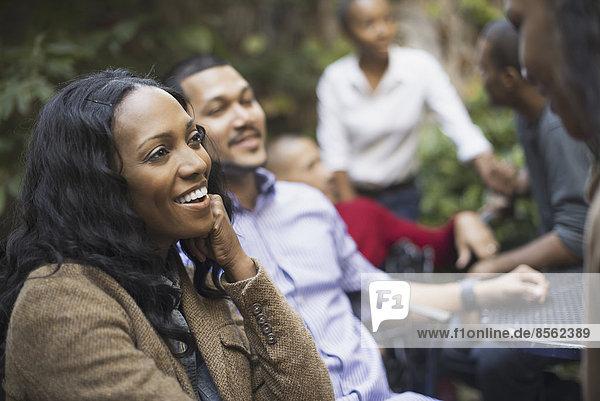 Szenen aus dem städtischen Leben in New York City. Eine Gruppe von Freunden sitzt zusammen auf einem begrünten Platz. Männer und Frauen.