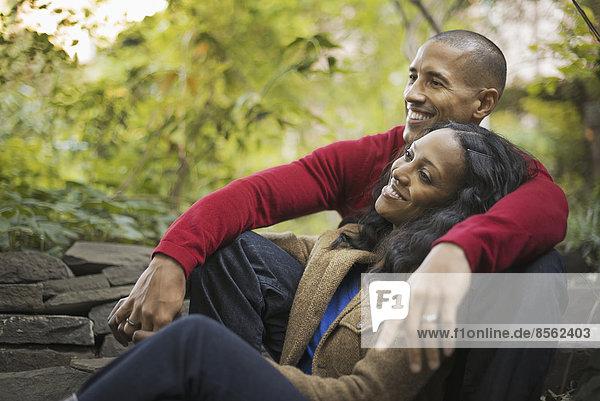 Szenen aus dem städtischen Leben in New York City. Ein Mann und eine Frau  ein Paar  das eng beieinander unter den Bäumen sitzt.