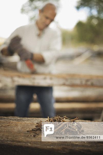 Ein Mann arbeitet auf einem ehemaligen Holzlager. Er benutzt ein Werkzeug  um Metalle aus einem Stück Altholz zu entfernen. Ein Haufen rostiger Metallnägel.