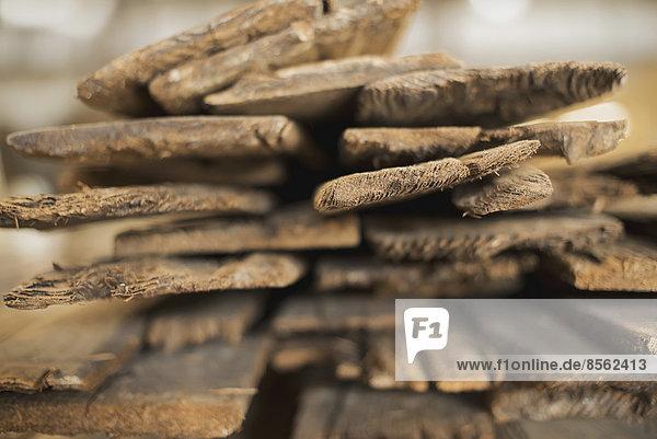 Ein Haufen recycelter Bohlen aus wiederverwertetem Altholz. Umweltgerechte Rückgewinnung in einem Holzlager.