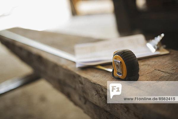 Ein wiedergewonnenes Holzlager. Recyceltes Brett aus Holz  Maßband und ein Klemmbrett mit Papierkram.