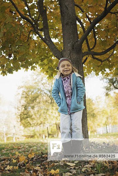 Ein junges Mädchen steht unter einem Baum  auf einem Bauernhof. Herbstliches Laub.