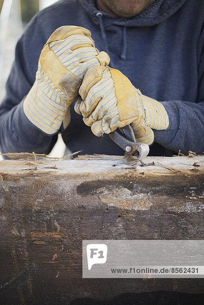 Eine zurückgewonnene Holzwerkstatt. Ein Mann bereitet das Holz vor  indem er alle Nägel und Bolzen entfernt.