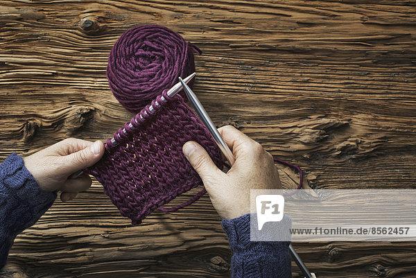Eine Frau hält zwei Stricknadeln und ein Stück Strickzeug in violetter Wolle.