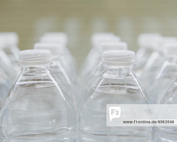 Reihen von mit Wasser gefüllten Plastikflaschen mit Schraubverschluss.