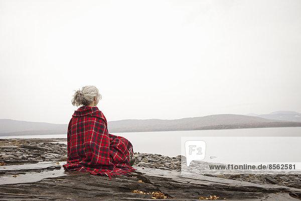 Eine Frau  die am Ufer eines ruhigen Sees über das Wasser schaut  eingehüllt in einen Schottenkaro-Teppich.