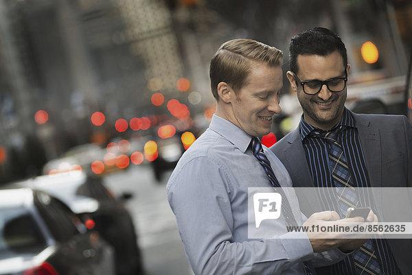 Zwei Männer stehen in der Dämmerung auf einer belebten Straße zusammen und schauen auf ein Handydisplay.