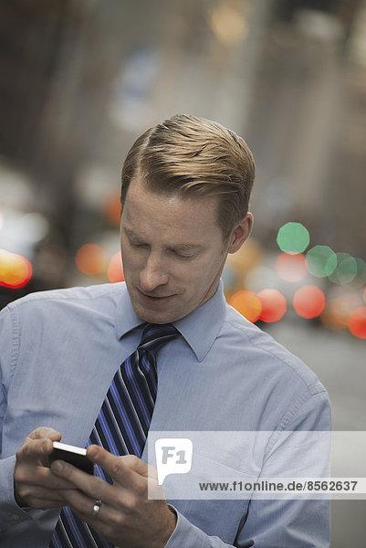 Ein Mann in Hemd und Krawatte,  der sein Handy überprüft,  steht auf einer belebten Straße.