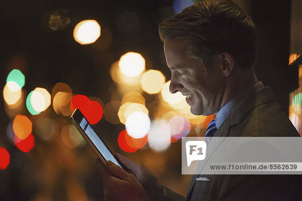 A man in a city at night  looking at a computer tablet.