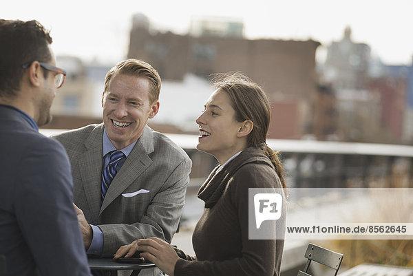 Drei Personen  die in einem offenen Raum zwischen Stadtgebäuden stehen und miteinander sprechen. Zwei Männer und eine Frau.