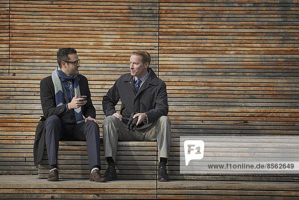 Zwei Männer sitzen auf einer Bank vor einem großen Gebäude in der Stadt. Einer überprüft sein Mobiltelefon.