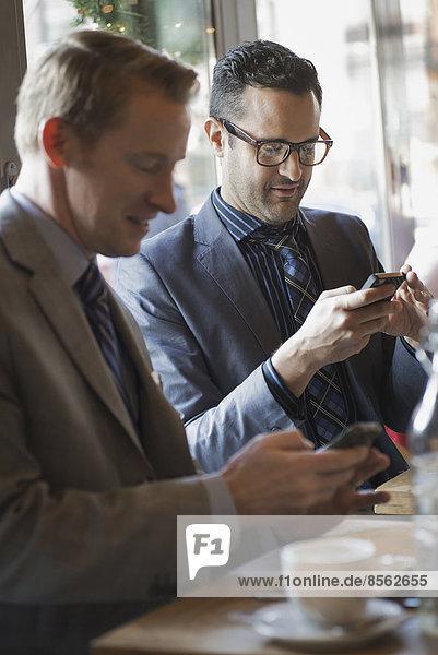 Geschäftsleute in der Stadt. Zwei Männer sitzen an einem Café-Tisch  überprüfen ihre Handy-Nachrichten und bleiben in Kontakt.