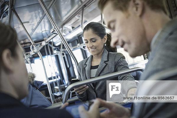 Geschäftsleute in der Stadt. Drei Personen in Bewegung  zwei Männer und eine Frau  im Bus.