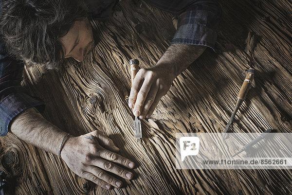 Ein Mann  der in einer wiederaufgearbeiteten Holzlagerhalle arbeitet. Halten von Werkzeugen und Schleifen von verästelten und unebenen Holzstücken.