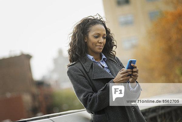 Stadtleben. Eine Frau im Mantel  Kontrolle und SMS  in Kontakt bleiben  ein Mobiltelefon benutzen.