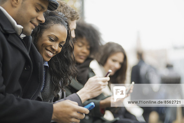 Stadtleben. Eine Gruppe von Menschen  die unterwegs sind  in Kontakt bleiben und Mobiltelefone benutzen. Männer und Frauen  die in einer Schlange stehen. Sie schauen auf und lachen.