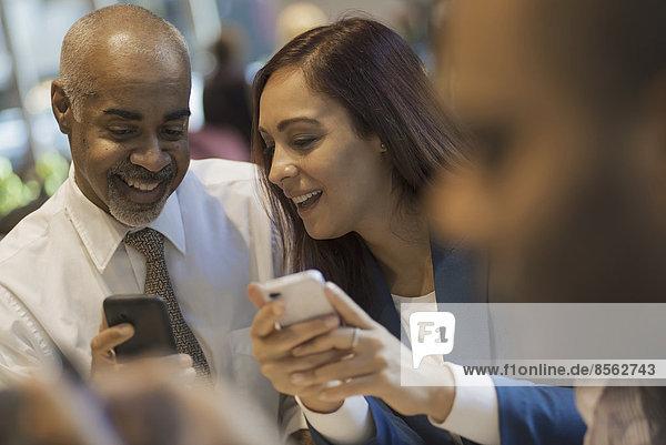 Stadtleben. Eine Gruppe von Menschen  die in einem Café sitzen  Mobiltelefone benutzen und miteinander reden.