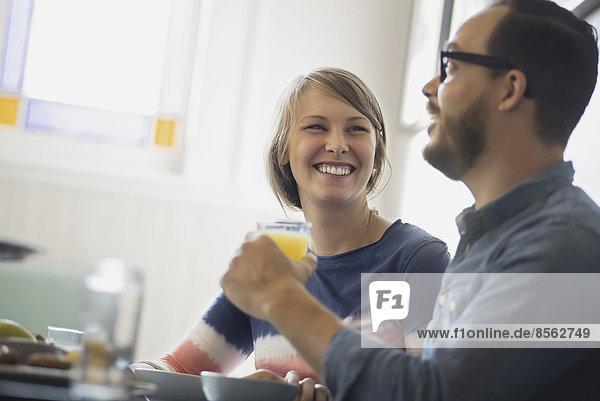 Ein Paar sitzt in einem Coffeeshop  lächelt und unterhält sich bei einer Tasse Kaffee.