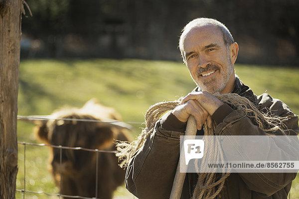 Ein Mann mit einem Holzstab und einer Seillänge neben einem Tiergehege. Eine Hochlandkuh mit Hörnern. Arbeit auf einem Biohof.