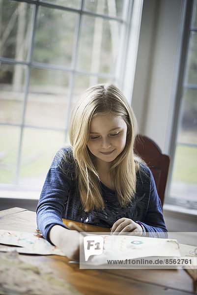 Ein Familienhaus. Ein junges Mädchen sitzt an einem Tisch und zeichnet auf ein großes Blatt Papier. Sie hält einen Bleistift in der Hand.