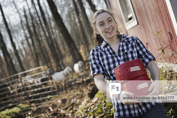 Eine junge Frau steht vor einem Gebäude eines Milchviehbetriebs  in dem sich zwei Käseblöcke befinden.