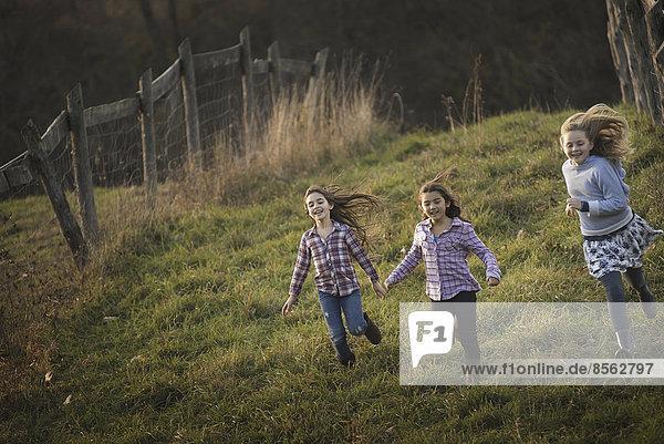 Three children running down a hill on an organic farm.