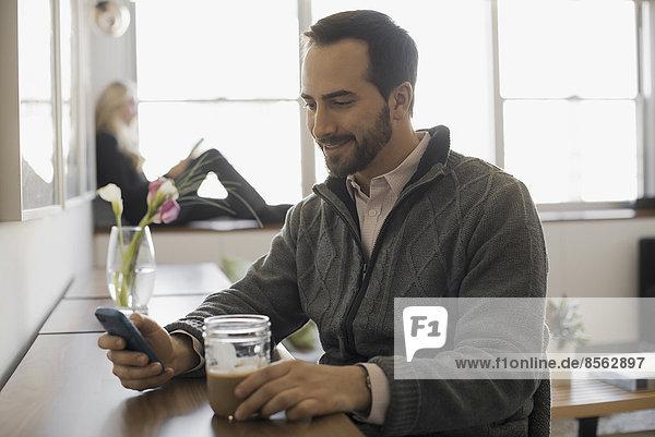 Paar  das sich zu Hause mit Laptop und E-Reader entspannt
