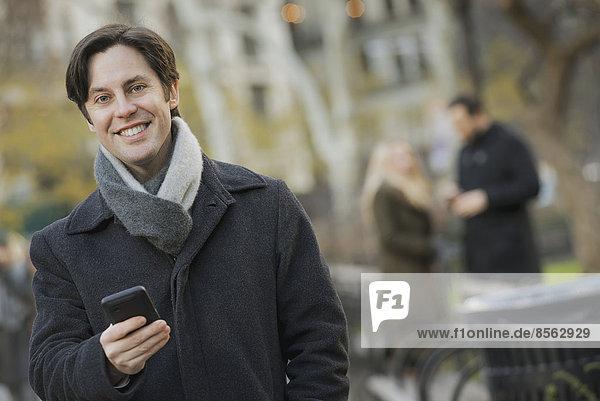 Mann im Stadtpark mit Smartphone