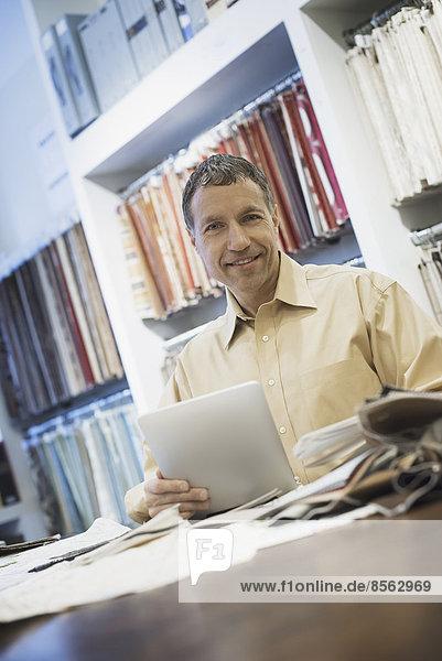 Mann arbeitet in Design-Werkstatt mit Tablette