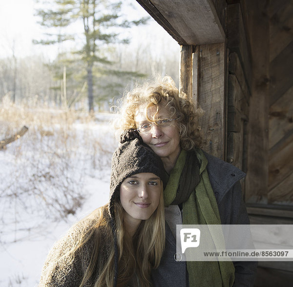 Two people  a mother and daughter  side by side  in the porch of a wooden barn on a farm. A winter's day.