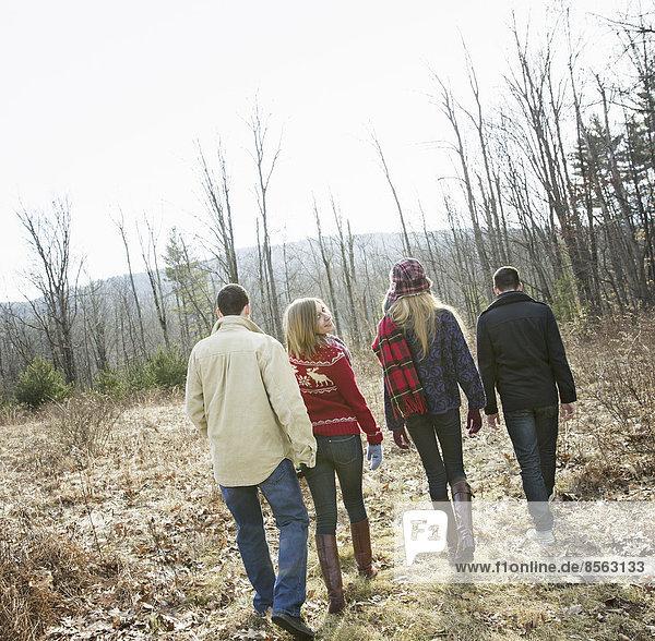 Eine Gruppe von vier Personen  die an einem Wintertag durch den Wald wandert. Zwei Männer und zwei Frauen.