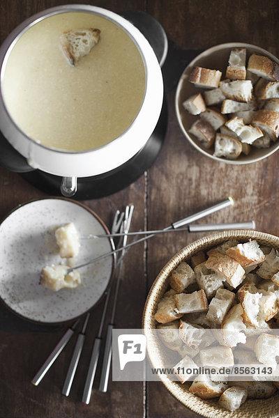 Ein Käsefondue auf einer Tischplatte. Brotwürfel und lange Gabeln  zum Eintauchen von Brot in eine reichhaltige geschmolzene Käsemischung.