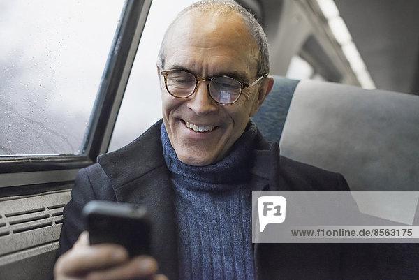 Ein reifer Mann  der in einem Zugwaggon am Fenster sitzt  sein Mobiltelefon benutzt und während der Fahrt in Kontakt bleibt.