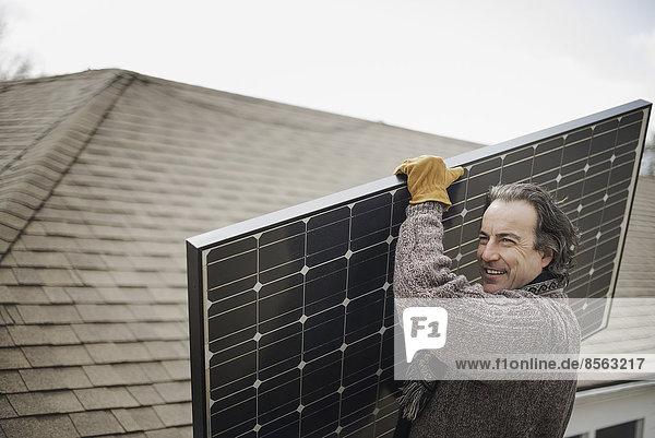 Ein Mann  der eine große Solaranlage über einen Bauernhof trägt.