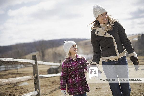 Eine Frau und ein Kind gehen bei Frühlingswetter Hand in Hand einen Weg auf einem Bauernhof entlang.
