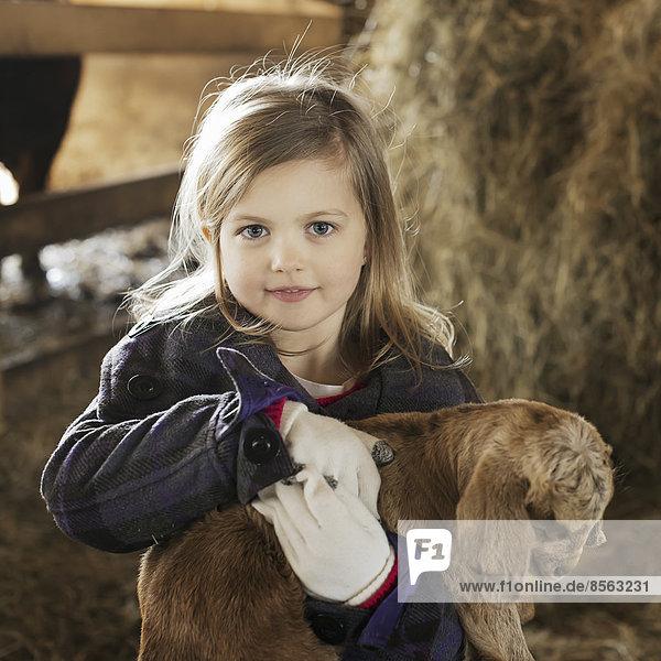 Ein Kind im Tierstall  das ein Ziegenbaby hält und streichelt.