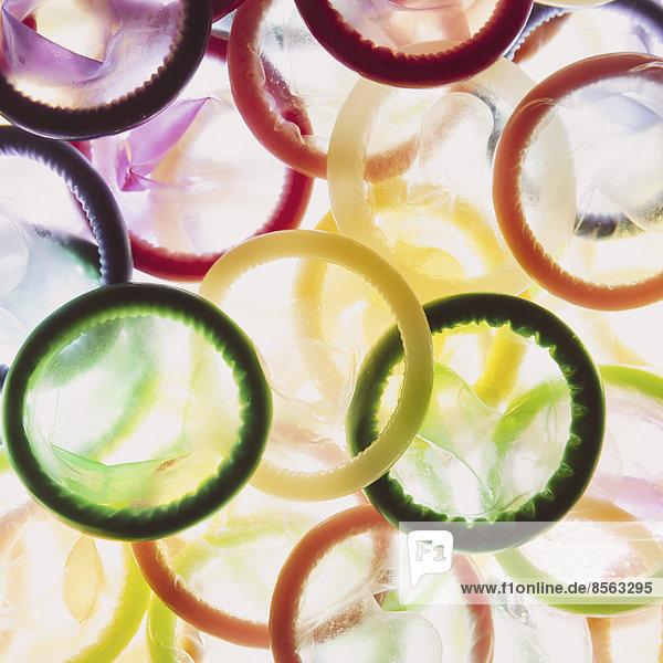 Eine große Gruppe von mehrfarbigen Kondomen auf weißem Hintergrund. Aufgehäuft.